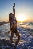 Menina que tem o divertimento na praia do mar foto de stock