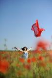Menina que tem o divertimento nas papoilas com o pano do vermelho do vôo Fotos de Stock
