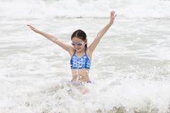 Menina que tem o divertimento no mar Fotografia de Stock