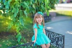 Menina que tem o divertimento no parque da cidade perto da árvore e na fonte que veste o vestido azul à moda que levanta e que so imagens de stock