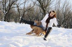 Menina que tem o divertimento no sledge Fotografia de Stock