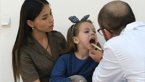 Menina que tem o exame da garganta por um doutor masculino foto de stock royalty free