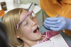 Menina que tem os dentes examinados na clínica dental foto de stock