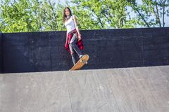Menina que tem skates de montada do divertimento no parque do patim imagens de stock royalty free