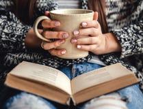 Menina que tem uma ruptura com o copo do café fresco após livros ou estudo de leitura foto de stock royalty free