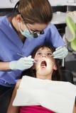 Menina que tem a verificação dental acima com dentista fêmea Fotografia de Stock Royalty Free