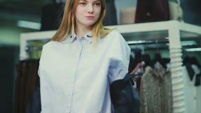Menina que tenta em um casaco de cabedal na loja filme