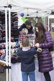 A menina que tenta na borda, em uma mulher com cabelo escuro e em um revestimento da beringela que olha a criança, o vendedor gua fotografia de stock royalty free