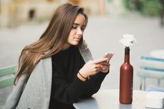 Menina que texting no telefone esperto na rua imagem de stock