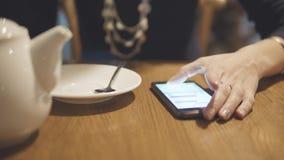 Menina que toca na tela com seu dedo Mulher que usa seu telefone celular no café filme