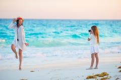 Menina que toma a foto da mãe nova na praia tropical no por do sol fotos de stock