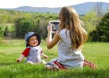Menina que toma a foto do bebê
