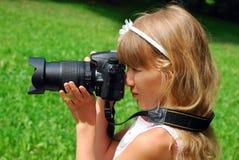 Menina que toma fotos pela câmera de reflexo profissional Fotos de Stock
