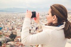 Menina que toma a imagem de uma cidade com seu telefone celular Imagem de Stock Royalty Free