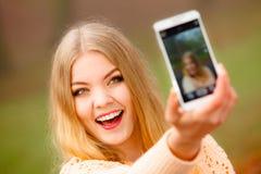 Menina que toma a imagem do auto com telefone fora Imagens de Stock