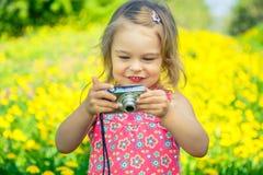 Menina que toma imagens em um prado Imagem de Stock Royalty Free