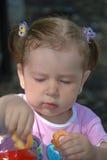 A menina que toma o bolinho Imagem de Stock Royalty Free