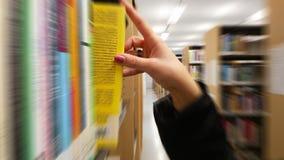 Menina que toma o livro de uma prateleira Foto de Stock Royalty Free
