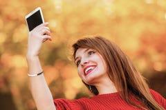 Menina que toma o selfie da imagem do auto com câmera do smartphone fora Imagem de Stock Royalty Free