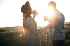 Menina que toma o sorvo do café com o noivo durante o por do sol Fotos de Stock Royalty Free
