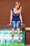 Menina que toma o tratamento do pedicure dos peixes, procedimento dos termas do garra do rufa Imagem de Stock