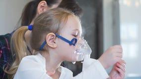 Menina que toma a terapia respiratória da inalação filme