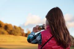 Menina que toma uma fotografia Fotografia de Stock Royalty Free