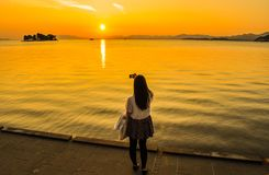 Menina que toma uma imagem do por do sol sobre um lago imagens de stock royalty free