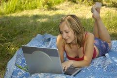 Menina que trabalha com o caderno ao ar livre imagens de stock royalty free