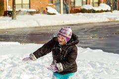 Menina que trabalha com pá a neve na maneira home da movimentação Jardim ou jardim da frente nevado bonito fotografia de stock royalty free