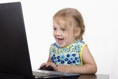A menina que trabalha em um portátil e em risos Imagem de Stock