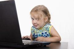 A menina que trabalha em um portátil e olhada misteriosamente no quadro Fotos de Stock