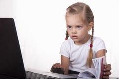 A menina que trabalha em um portátil, folheando através de um diário Fotografia de Stock