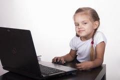 A menina que trabalha em um portátil, obtem confundida e olhada um pouco fora do quadro Imagem de Stock