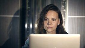 Menina que trabalha no computador na noite no interior com fundo da água filme