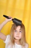 Menina que treying para escovar seu cabelo foto de stock royalty free