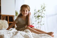 Menina que usa dispositivos diferentes em casa imagens de stock royalty free