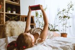 Menina que usa dispositivos diferentes em casa imagens de stock