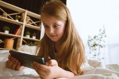 Menina que usa dispositivos diferentes em casa fotografia de stock