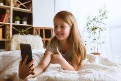 Menina que usa dispositivos diferentes em casa fotografia de stock royalty free