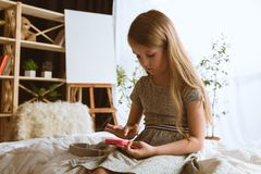 Menina que usa dispositivos diferentes em casa imagem de stock royalty free