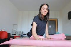 Menina que usa licenças de parto para fazer os acessórios de couro Foto de Stock