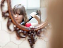 Menina que usa o ferro de ondulação antes do espelho imagens de stock royalty free
