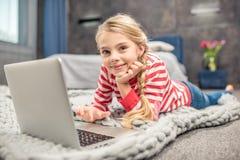 Menina que usa o portátil Fotografia de Stock Royalty Free