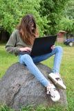 Menina que usa o portátil fora fotografia de stock royalty free