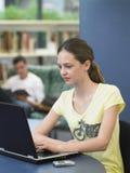Menina que usa o portátil na biblioteca fotos de stock