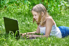 Menina que usa o portátil na grama Fotografia de Stock