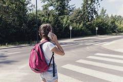 Menina que usa o smartphone ao andar atrav?s do cruzamento pedestre imagens de stock royalty free