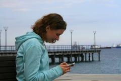Menina que usa o smartphone no beira-mar fotografia de stock
