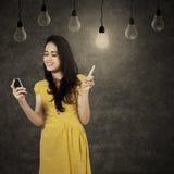 Menina que usa o telefone celular sob lâmpadas Foto de Stock Royalty Free